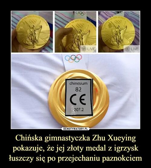 Chińska gimnastyczka Zhu Xueying pokazuje, że jej złoty medal z igrzysk łuszczy się po przejechaniu paznokciem